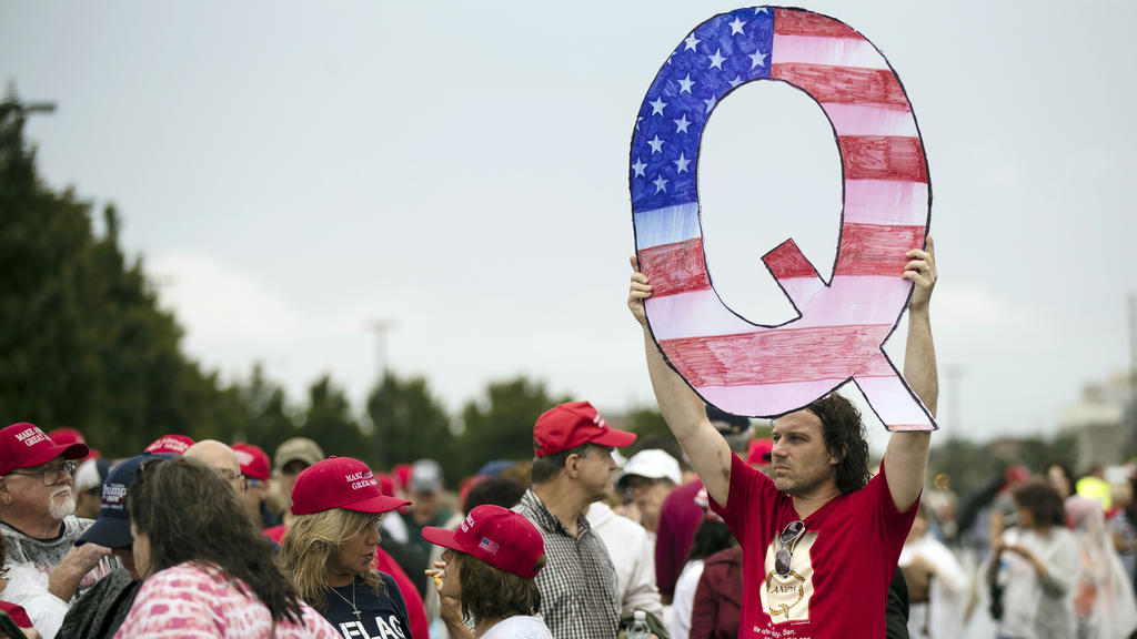 David Reinert holding a Q sign waits in line with others to enter a campaign rally with President Donald Trump and U.S. Senate candidate Rep. Lou Barletta, R-Pa., Thursday, Aug. 2, 2018, in Wilkes-Barre, Pa. (AP Photo/Matt Rourke)