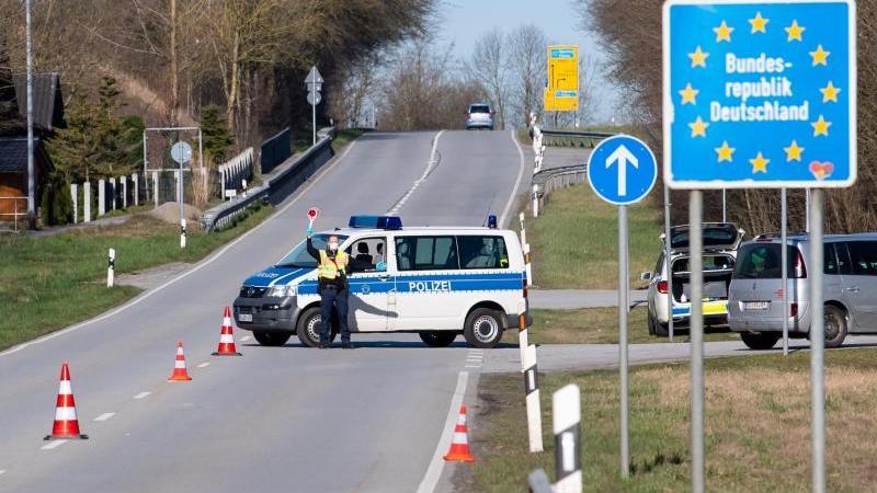 Polizisten stehen an einer Kontrollstelle an der Grenze zu Österreich. Foto: Sven Hoppe/dpa/Archivbild