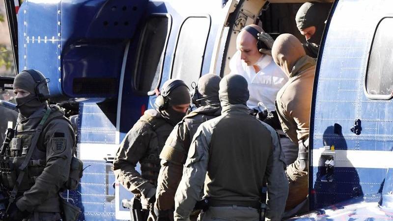 Stephan B., der Attentäter von Halle, wird von Polizisten aus einem Hubschrauber gebracht. Foto: Uli Deck/dpa