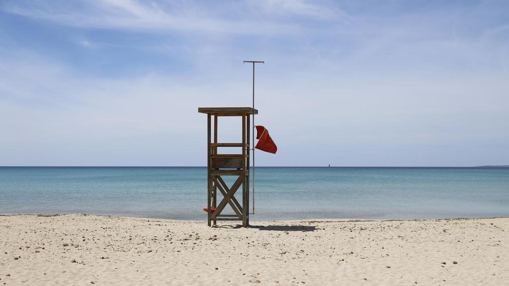 07.05.2020, Spanien, Palma: Eine rote Flagge weht am Strand von Arenal, um das Schwimmen zu verbieten. Die Abwesenheit von Touristen ist an den Stränden Mallorcas spürbar. «Das Wasser ist derzeit spektakulär transparent», sagt der Biologe Txema Broto