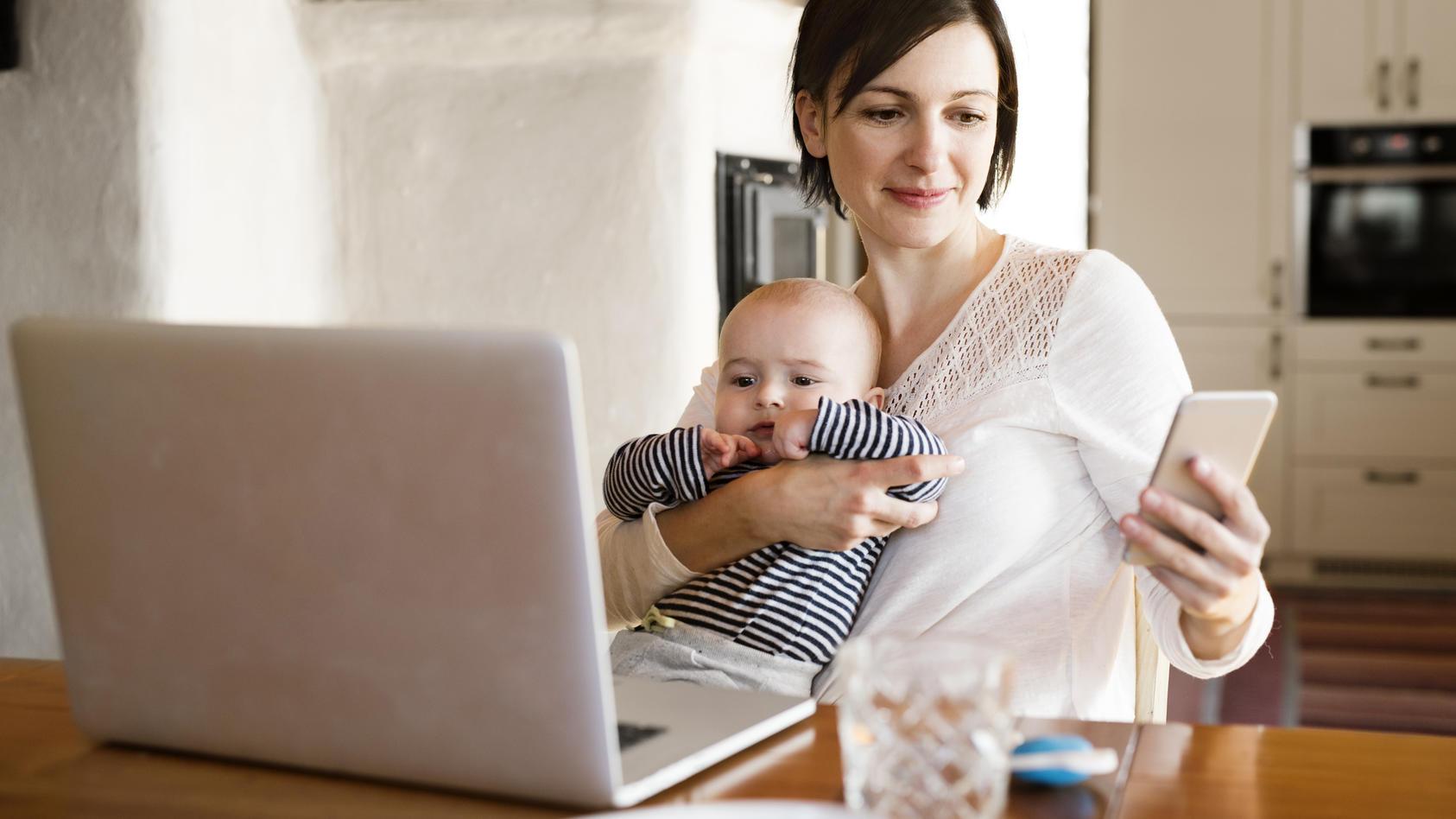 Eine Mutter schaut auf ihr Smartphone, während sie ihr Kind auf dem Arm hat.