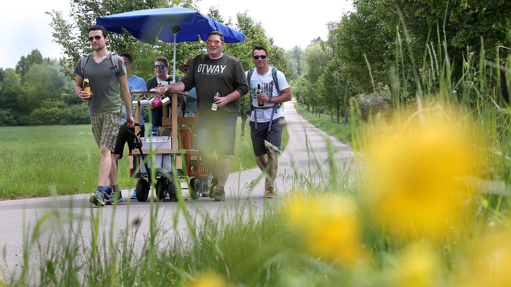 Eine Gruppe Männer ist am 25.05.2017 bei ihrer Vatertagstour mit Handwagen und einem Sonnenschirm bei Erisdorf (Baden-Württemberg) unterwegs. Foto: Thomas Warnack/dpa | Verwendung weltweit