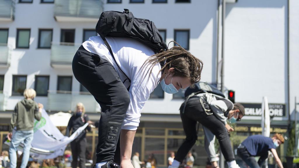 15.05.2020, Hessen, Frankfurt/Main: Einen Slogan sprühen Teilnehmer der Fridays for Future Demonstration auf den Asphalt. Es ist die erste reguläre Versammlung der Klimaaktivisten in Frankfurt nach drei Monaten. Foto: Sebastian Kramer/dpa +++ dpa-Bil