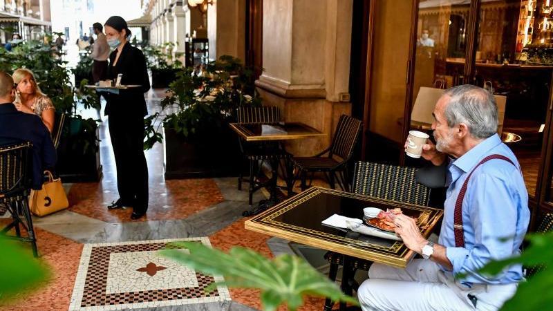 Gäste sitzen mit Abstand zueinander an Tischen in einem Café in Mailand. Foto: Claudio Furlan/LaPresse via ZUMA Press/dpa