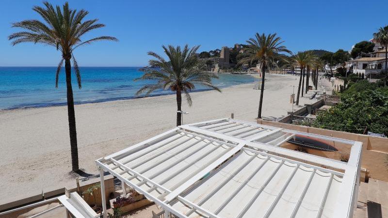 Der menschenleere Strand von Paguera auf der spanischen Insel Mallorca. Die Hoffnung auf Grenzöffnungen für den Sommerurlaub wächst von Tag zu Tag. Foto: Clara Margais/dpa