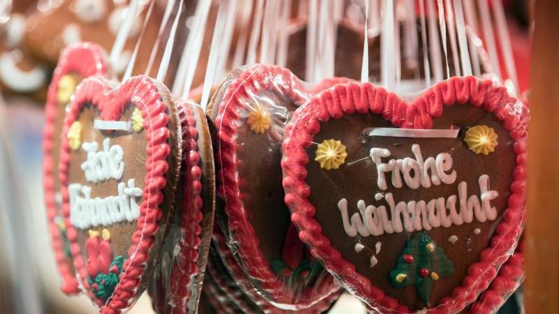 """Lebkuchenherzen mit der Aufschrift """"Frohe Weihnacht"""" hängen an einem Stand. Foto: Soeren Stache/dpa/Archivbild"""