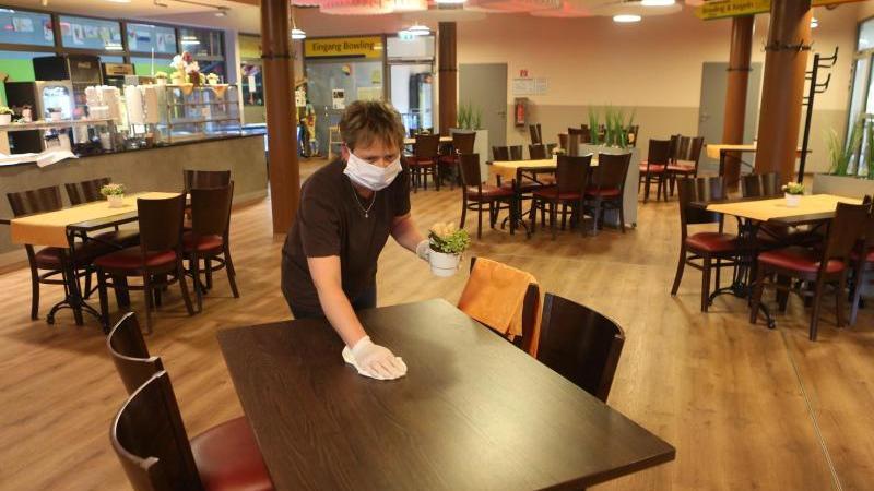Eine Mitarbeiterin reinigt und desinfiziert einen Tisch in einem Restaurant in Wernigerode. Foto: Matthias Bein/dpa-Zentralbild/dpa/Archivbild