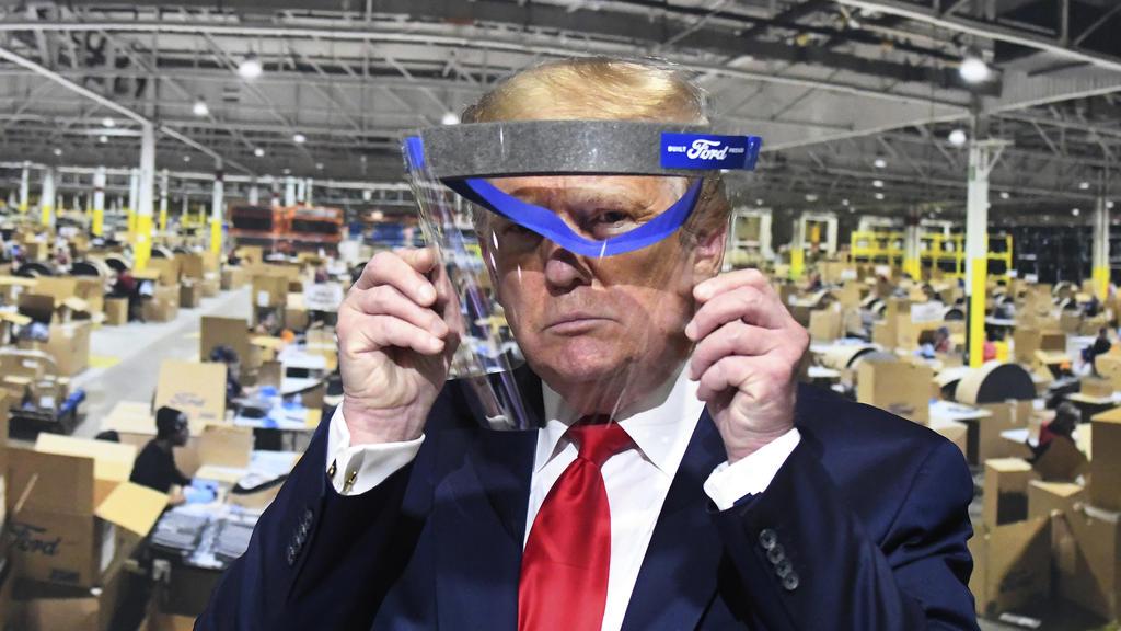 dpatopbilder - 21.05.2020, USA, Ypsilanti: Donald Trump, Präsident der USA, schaut während eines Rundgangs in einem Ford-Werk durch ein Gesichtsvisier vor einem Plakat, das die Fertigung der Visiere zeigt. Bei seinem Besuch hat er zeitweise erneut ke