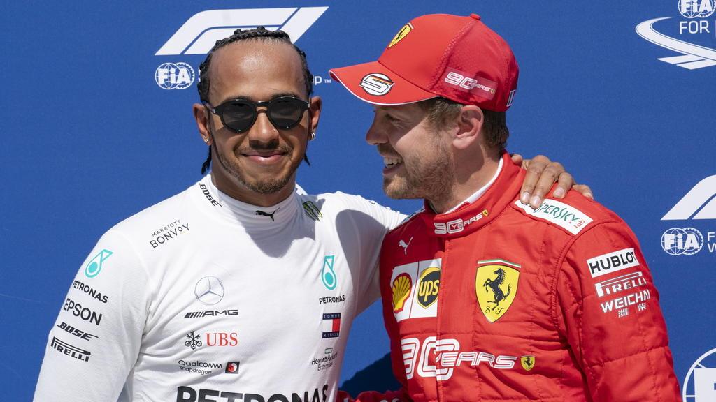 ARCHIV - 08.06.2019, Kanada, Montreal: Motorsport: Formel-1-Weltmeisterschaft, Grand Prix von Kanada, Qualifying: Lewis Hamilton (l) aus Großbritannien vom Team Mercedes gratuliert Sebastian Vettel aus Deutschland vom Team Scuderia Ferrari zur Pole-P