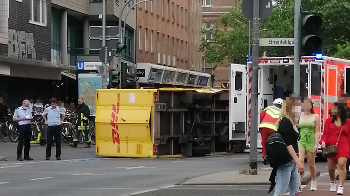 DHL-Wagen kippt in Köln auf der Straße um.