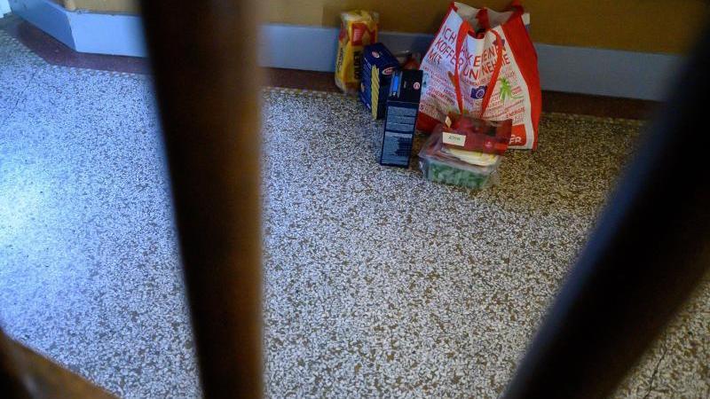Einkäufe für auf Corona positiv getestete Personen stehen in einem Hausflur. Foto: Sebastian Gollnow/dpa/Archivbild
