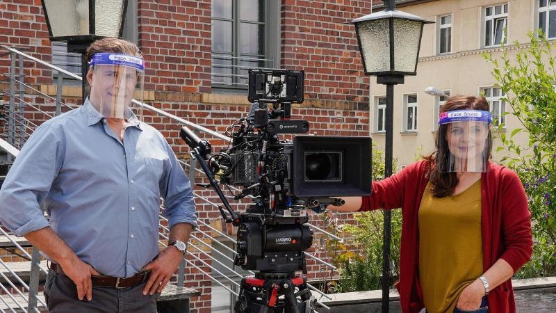 Die Schauspieler Sven Martinek (Rolle Dr. Christoph Lenz) und Elisabeth Lanz (Rolle Tierärztin Dr. Mertens) tragen Plastikvisiere zum Schutz gegen das Coronavirus. Foto: Steffen Junghans/ARD/dpa