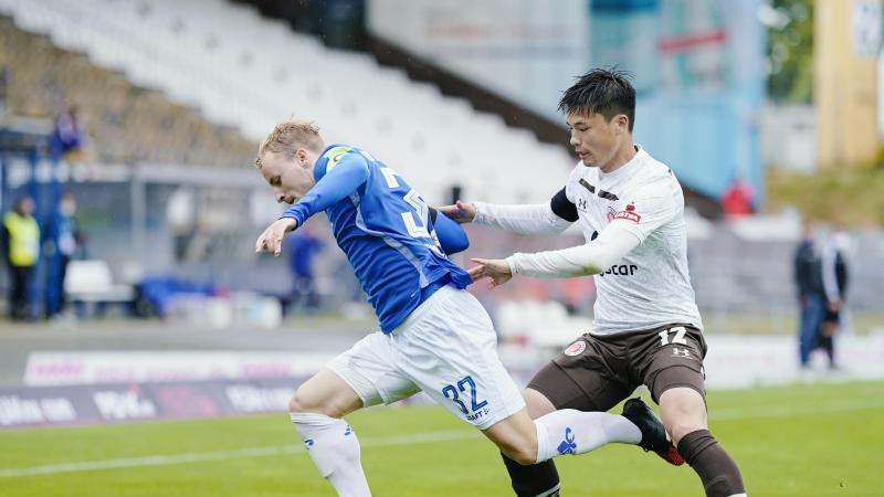 Darmstadts Fabian Holland in Aktion gegen St. Paulis Ryo Miyaichi (l-r). Foto: Uwe Anspach/dpa-Pool/dpa