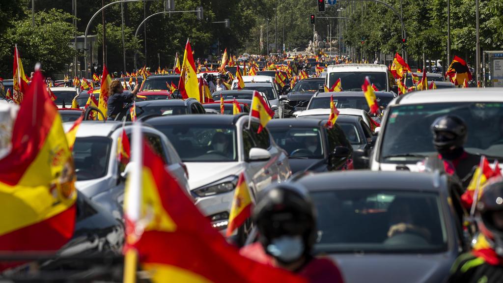 23.05.2020, Spanien, Madrid: Anhänger der rechtspopulistischen Partei Vox schwenken bei einer Demonstration die Nationalflagge von Spanien. Tausende haben bei Kundgebungen in ganz Spanien gegen die Anti-Corona-Maßnahmen den Rücktritt des sozialistisc