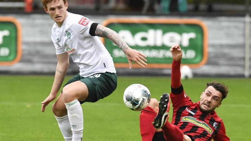 Josh Sargent von Bremen und Manuel Gulde von Freiburg (l-r.) im Zweikampf um den Ball. Foto: Thomas Kienzle/AFP-Pool/dpa