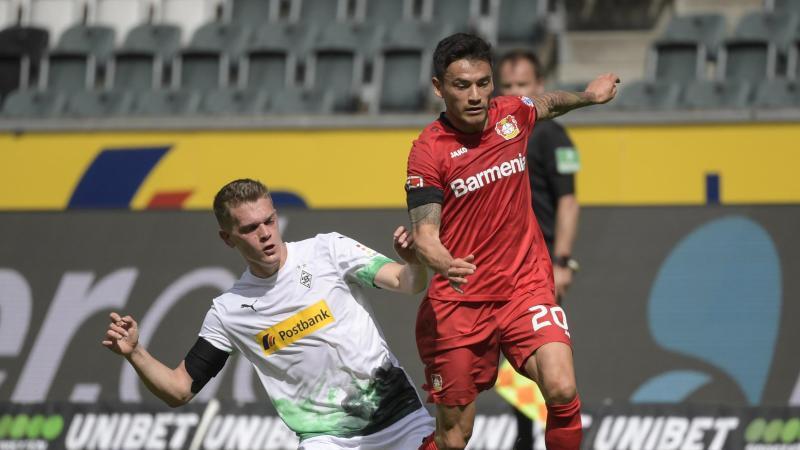 Mönchengladbachs Matthias Ginter und Charles Mariano Aranguiz aus Leverkusen (l-r.) in Aktion. Foto: Ina Fassbender/AFP-Pool/dpa