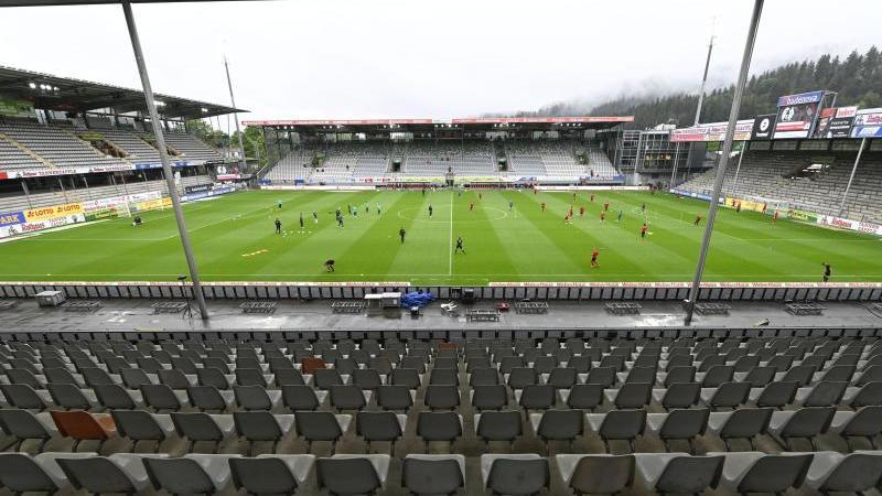 Spieler von Freiburg und Bremen wärmen sich vor dem Spiel im leeren Stadion auf. Foto: Thomas Kienzle/AFP-Pool/dpa