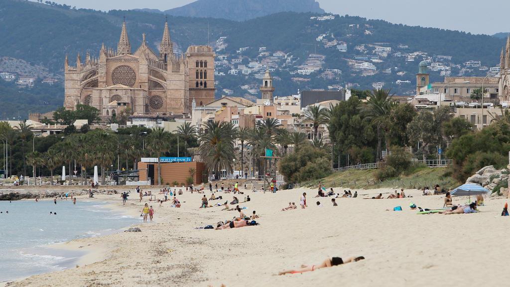 25.05.2020, Spanien, Palma De Mallorca: Badegäste liegen am Strand Playa de Palma. Nach einer mehr als zweimonatigen Zwangsschließung wegen der Corona-Pandemie haben Mallorca und viele andere Regionen Spaniens am Montag ihre Strände wieder geöffnet.