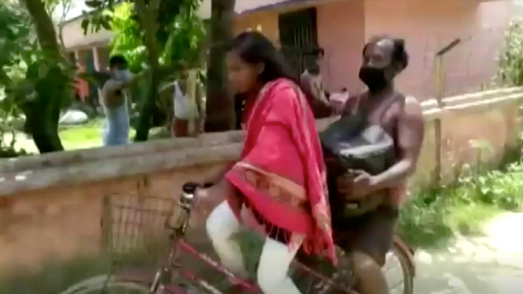 Jyoti Kumari carries her father on the back of her bicycle, in Darbhanga, Bihar, India May 21, 2020 in this still image taken from?video.?ANI via REUTERS TV ATTENTION EDITORS - THIS IMAGE HAS BEEN SUPPLIED BY A THIRD PARTY. INDIA OUT. NO COMMERCIAL O