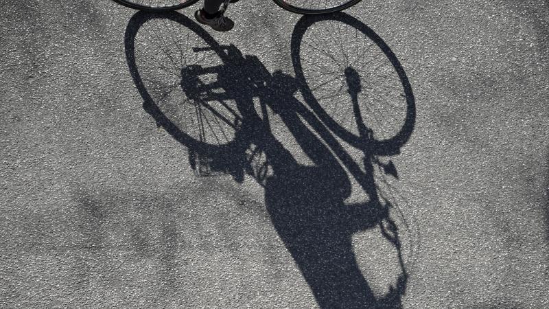 Ein Fahrradfahrer wirft einen langen Schatten auf den Asphalt einer Straße. Foto: Marcus Brandt/dpa/Symbolbild