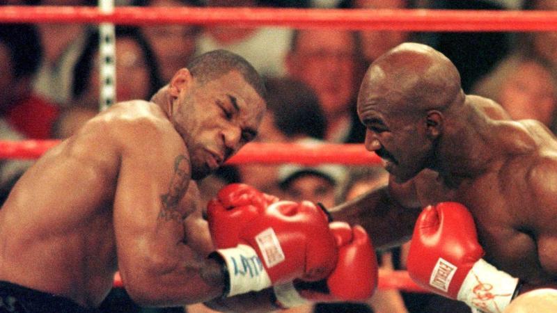 Mike Tyson (l) und Evander Holyfield beim WM-Kampf 1997 in Las Vegas. Foto: John Gurzinsky/epa/dpa
