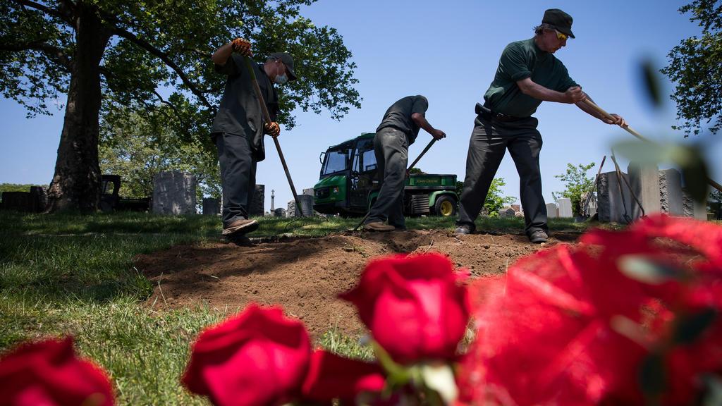"""26.05.2020, USA, New York: Mitarbeiter des Friedhofs """"Calvary Cemetery"""" arbeiten während der Corona-Pandemie an einem Grab. Foto: Michael Nagle/XinHua/dpa +++ dpa-Bildfunk +++"""