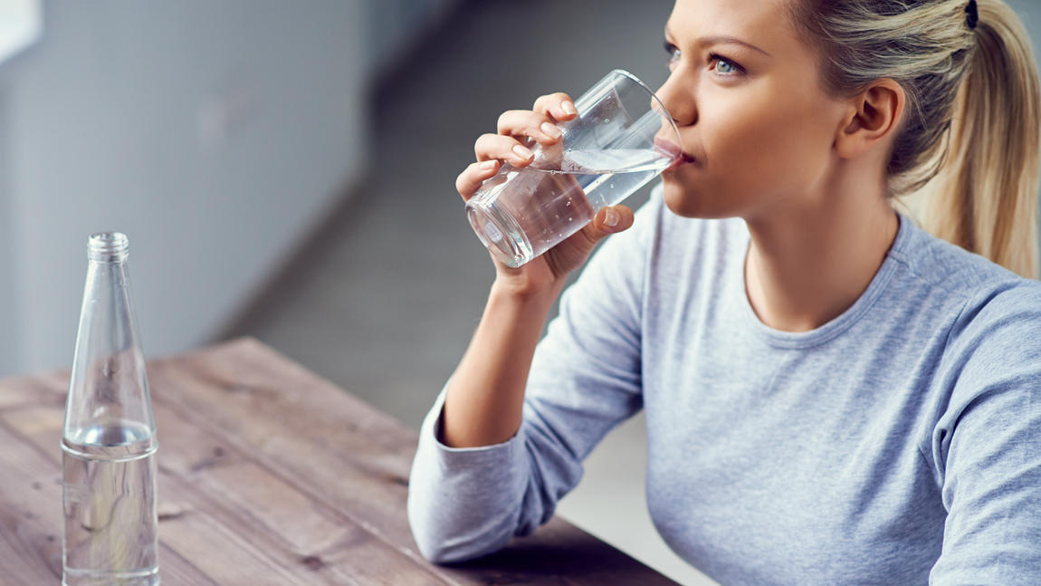 Junge Frau trinkt morgens Wasser