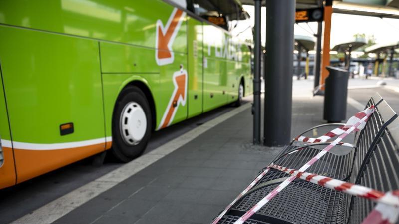 Ein Flixbus steht im Zentralen Omnibusbahnhof in Berlin neben einer abgesperrten Sitzreihe. Foto: Fabian Sommer/dpa