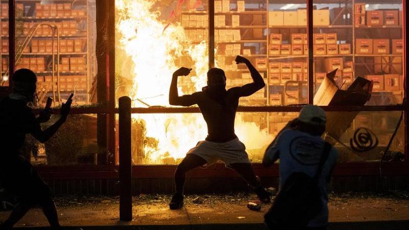 Ein Mann posiert während der gewaltsamen Proteste in Minneapolis vor einem Feuer einem Geschäft. Foto: Carlos Gonzalez/Star Tribune/AP/dpa