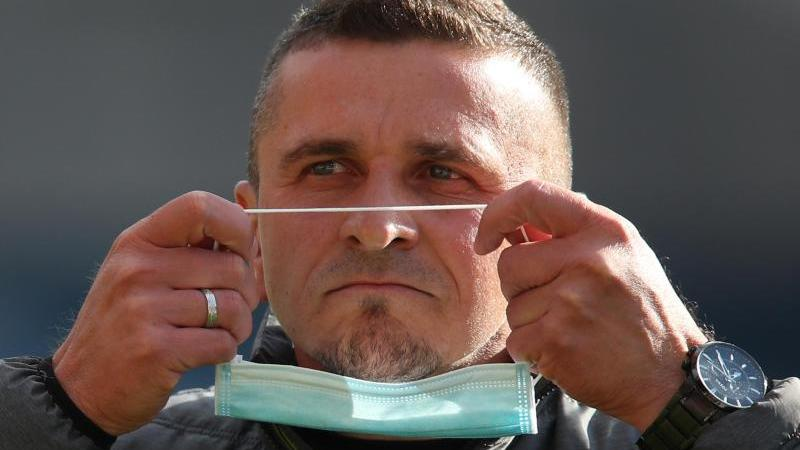 Trainer Mersad Selimbegovic von Regensburg setzt eine Maske vor dem Spiel auf. Foto: Daniel Karmann/dpa-Pool/dpa/Archivbild