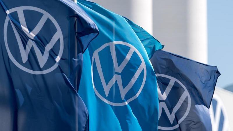 Fahnen mit dem VW-Logo wehen vor einem Fahrzeugwerk. Foto: Hendrik Schmidt/dpa-Zentralbild/ZB/Symbolbild