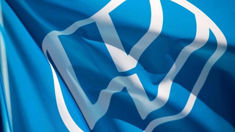 Eine Fahne mit dem VW-Logo weht. Foto: Hendrik Schmidt/dpa-Zentralbild/dpa/Archivbild