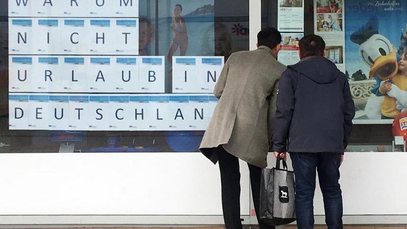 """Zwei Männer schauen in das Schaufenster eines Reisebüros, an dem mit großen Buchstaben """"Warum nicht Urlaub in Deutschland"""" zu lesen ist. Foto: Bernd Thissen/dpa"""