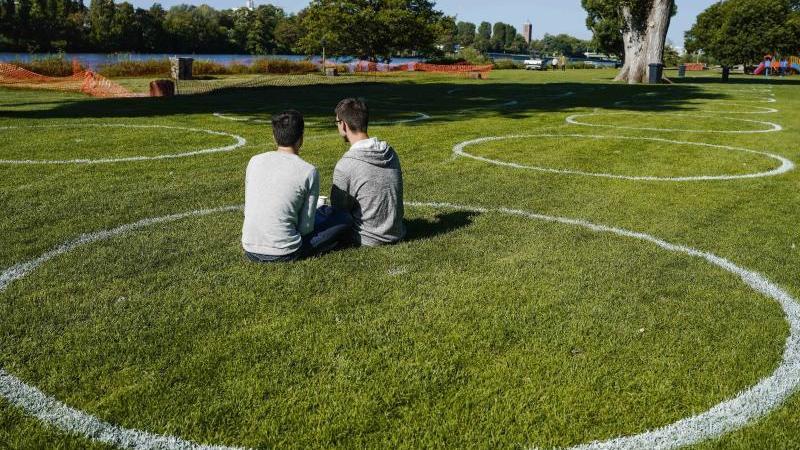 Zwei Besucher sitzen auf der Neckarwiese in einem mit spezieller Farbe gemalten Kreis. Foto: Uwe Anspach/dpa