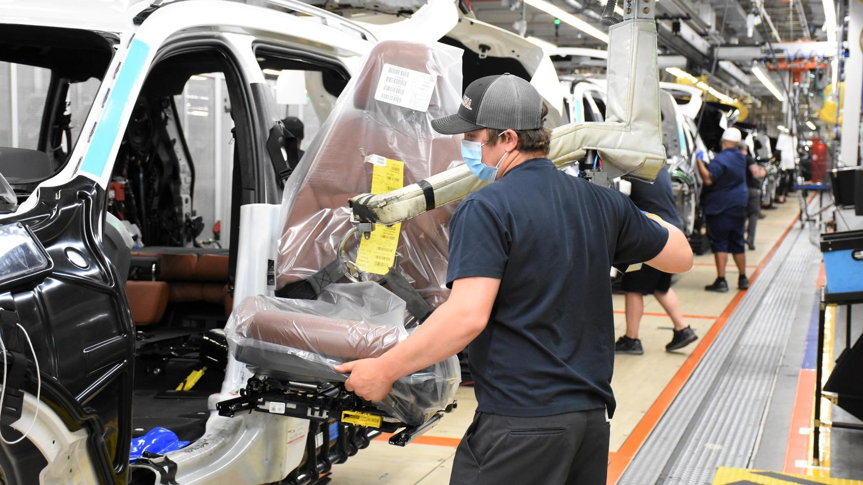 BMW-Arbeiter montieren einen SUV.