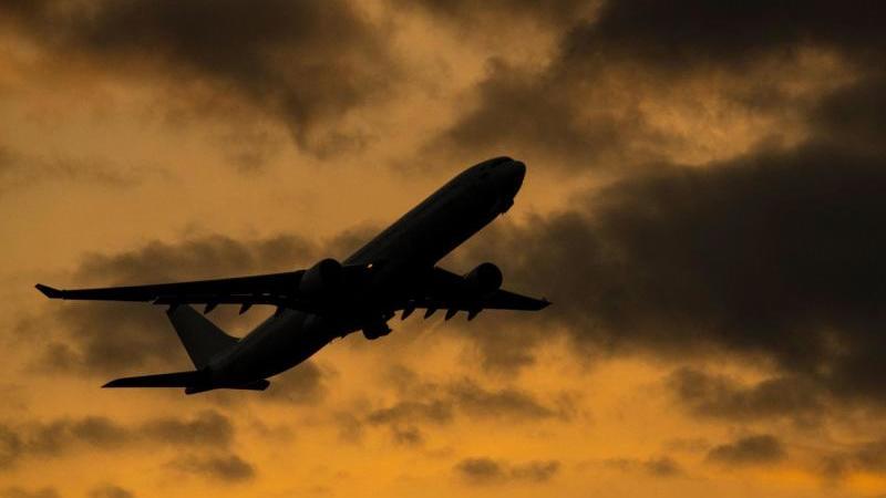 Ein Flugzeug startet vom Flughafen Frankfurt vor dem roten Abendhimmel. Foto: Boris Roessler/dpa