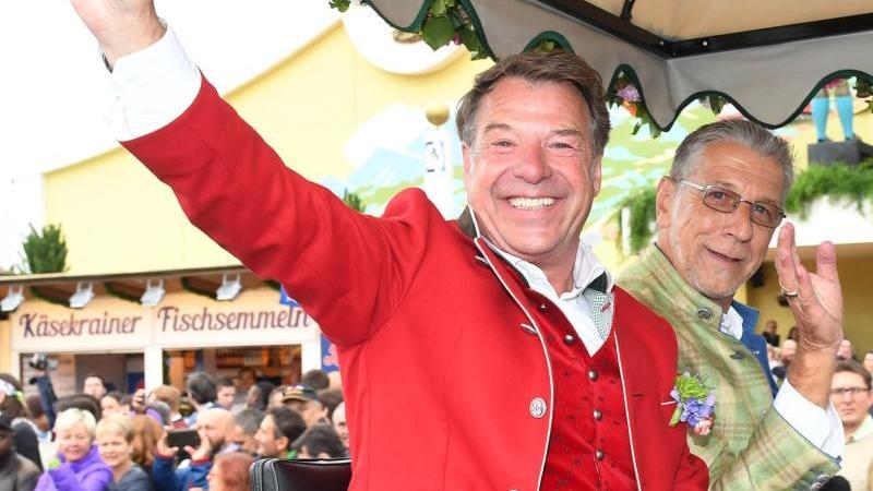 Der Schlagersänger Patrick Lindner (l.) und sein Lebensgefährte Peter Schäfer winken. Foto: picture alliance/Tobias Hase/dpa/Archivbild