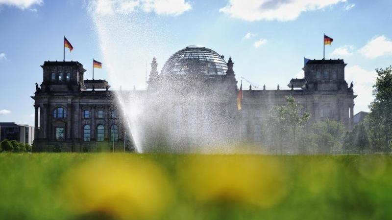 Ein Rasensprenger berieselt bei Sonnenschein die Wiese vor dem Reichtagsgebäude. Foto: Kay Nietfeld/dpa
