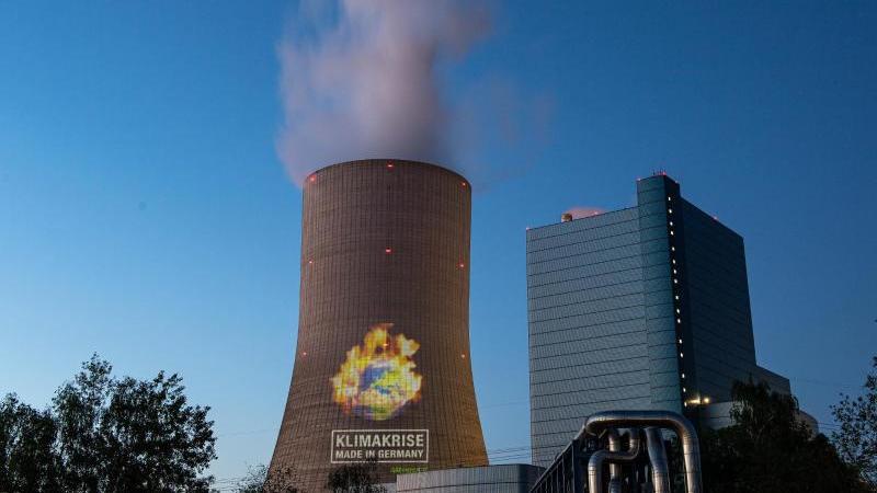 Aktivisten projektieren bei einer Protestaktion einen Schriftzug auf den Kühlturm von Datteln 4. Foto: Guido Kirchner/dpa