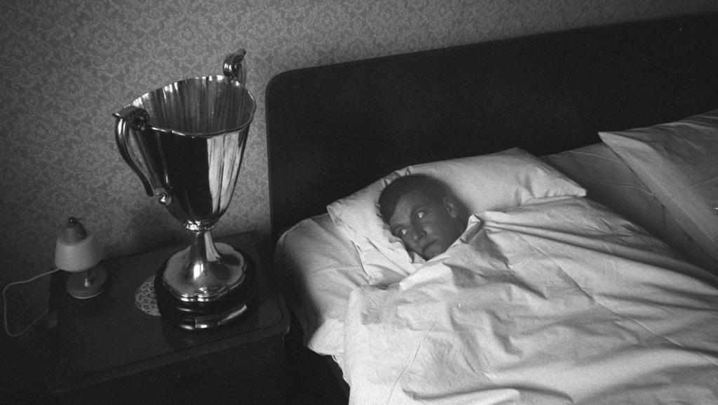 Franz Bulle ROTH liegt im Bett und schaut auf den Europapokal, der auf dem Nachttisch steht,