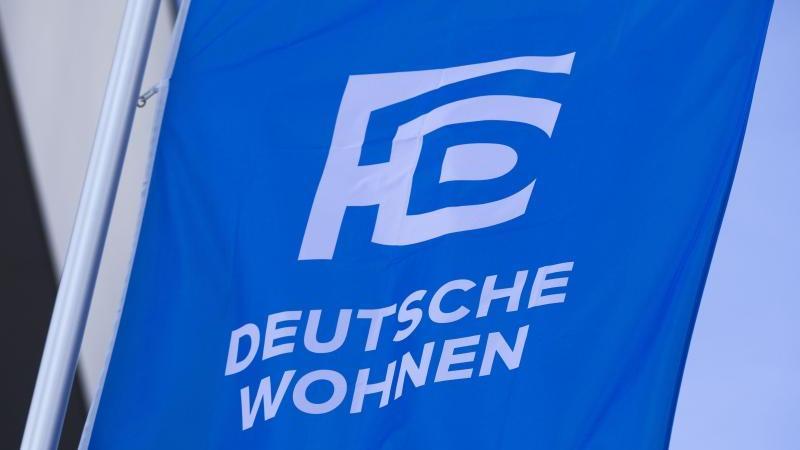 Das Logo des Immobilienkonzerns Deutsche Wohnen ist am Morgen auf einer Fahne vor dem Eingang zur Hauptversammlung des Unternemens zu sehen. Foto: Frank Rumpenhorst/dpa/archivbild