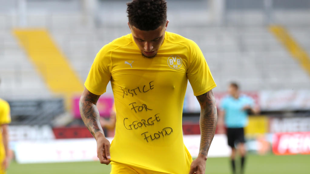 PADERBORN, GERMANY - MAY 31: Jadon Sancho of Borussia Dortmund celebrates scoring his teams second goal of the game with a 'Justice for George Floyd' shirt during the Bundesliga match between SC Paderborn 07 and Borussia Dortmund at Benteler Arena on