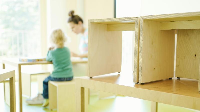 Eine Erzieherin und ein Kind spielen hinter auf den Tisch gestellten Stühlen. Foto: Uwe Anspach/dpa/Archivbild