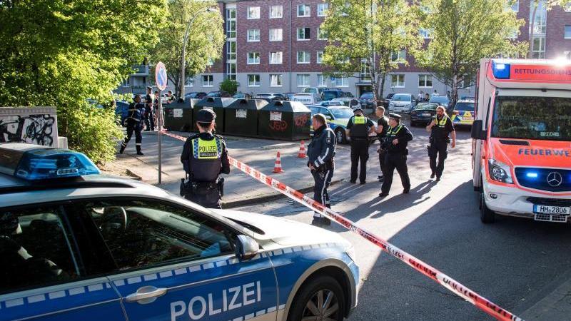 Einsatzkräfte von Polizei und Rettungsdienst stehen im Stadtteil Bergedorf am Tatort. Foto: Daniel Bockwoldt/dpa/Archivbild
