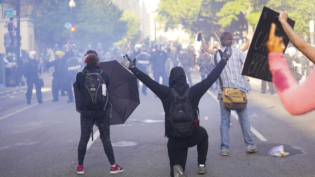 01.06.2020, USA, Washington: Demonstranten stehen während eines Protests vor Polizisten. Landesweite Proteste richten sich nach dem gewaltsamen Tod des Afroamerikaners Floyd durch einen weißen Polizisten gegen Rassismus und Polizeigewalt. Die teils s