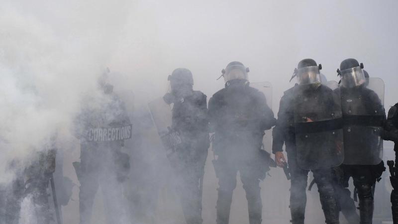 Polizisten während eines Protests in Atlanta inmitten einer Tränengaswolke. Foto: Ben Gray/Atlanta Journal-Constitution/AP/dpa