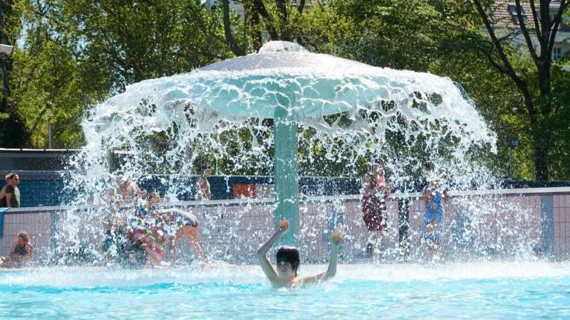Ein Wasserpilz im Prinzenbad ist in Betrieb, Kinder tummeln sich im Schwimmbecken. Foto: Annette Riedl/dpa/Archivbild