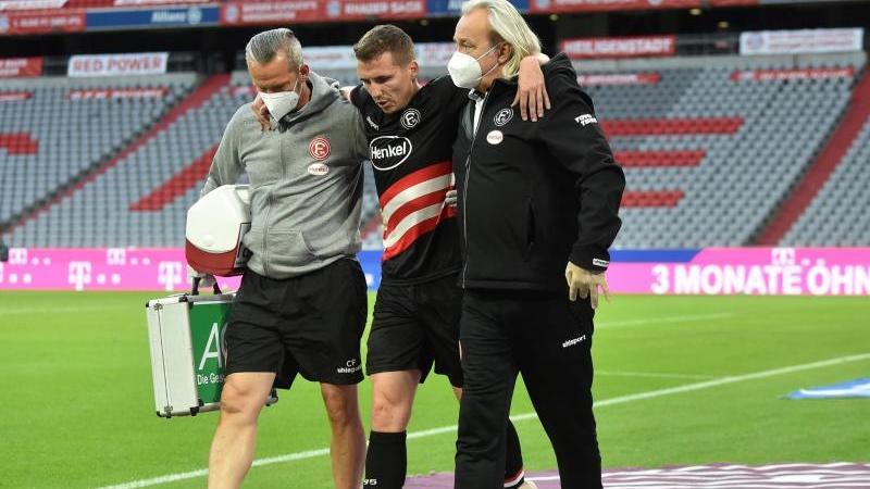 Der verletzte Marcel Sobottka (M.) von Fortuna Düsseldorf wird gestützt vom Platz begleitet. Foto: Christof Stache/AFP/Pool/dpa
