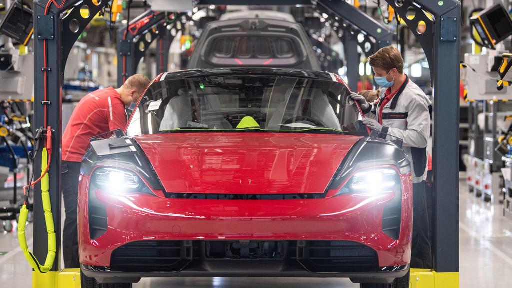 ARCHIV - 12.05.2020, Baden-Württemberg, Stuttgart: Mitarbeiter der Porsche AG tragen in der Produktion des elektrisch angetriebenen Porsches Taycan Masken. Mit einem Milliardenpaket will die Große Koalition die Wirtschaft in der Corona-Krise ankurbel