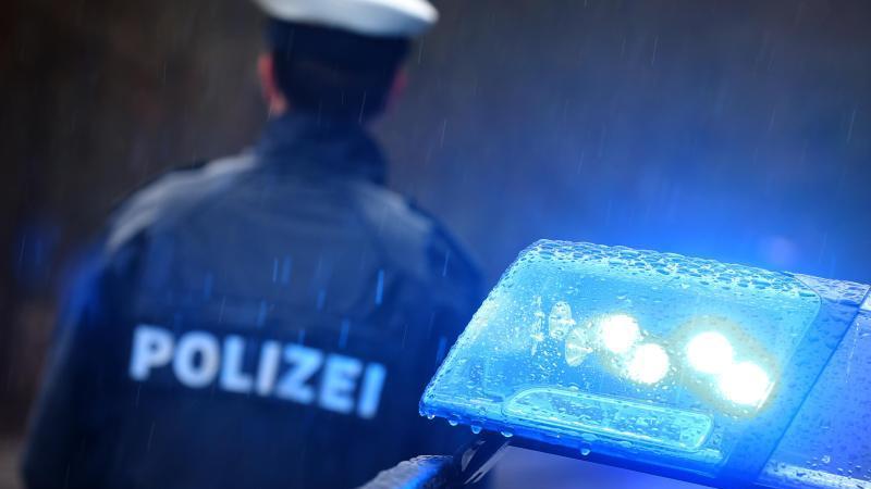 Ein Polizist steht vor einem Streifenwagen dessen Blaulicht aktiviert ist. Foto: Karl-Josef Hildenbrand/dpa/Archivbild